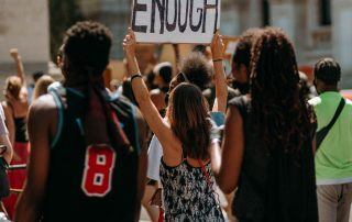 "Activists walk with a sign that says ""Enough"""