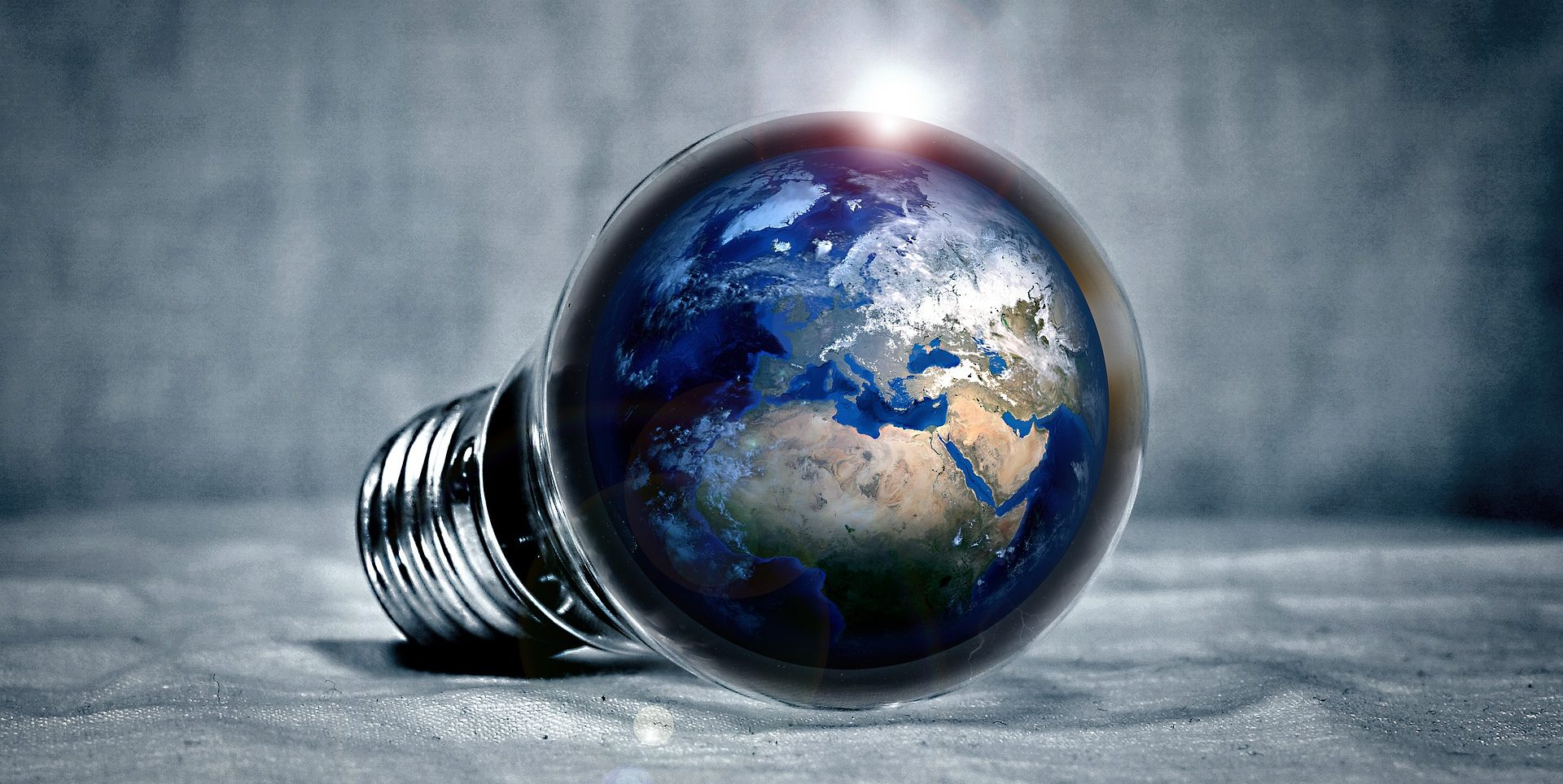 A light bulb laying on its side with the main part of the bulb looking like a globe.