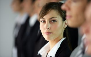 Young woman standing in line with co-workers. She is the only one in focus. She is looking to her left at the camera with a slight smile.