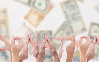 The word donation spelled out using human hands in front of different currencies.