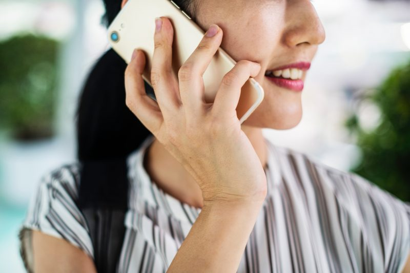 Image of a woman on the phone. Photo by rawpixel on Unsplash.