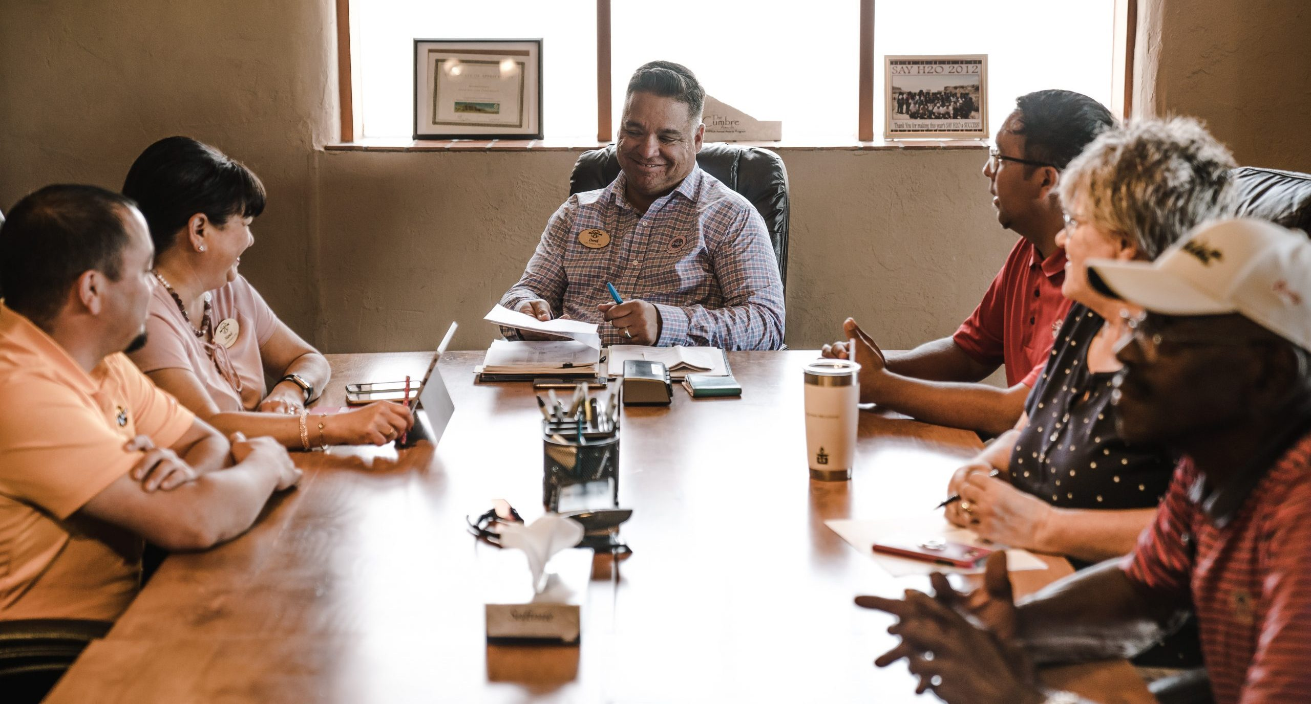 A group of men and women of various ages and ethnicities sit around a meeting table.