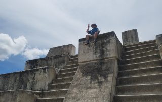 A young man (new JVA associate consultant Jessi Rodriguez) sits at the top of Mayan ruins.