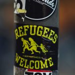 """A sticker on a pole that says """"Refugees welcome"""" and has a drawing of the silhouettes of two adults and a child fleeing."""