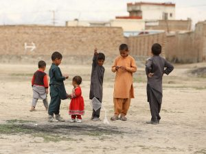 A group of children in Kabul, Afghanistan. A boy is holding a small kite.